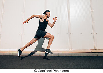 Young man runner running along wall with copy space