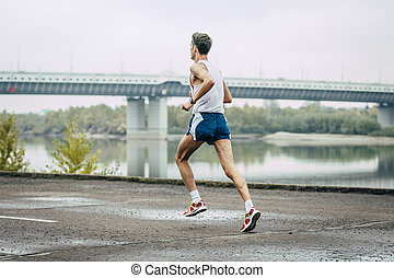 young man running along embankment