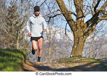 Young man running athlete during a workout in a hill