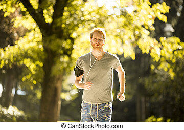 Young man running in the autumn park