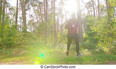 Young Man Running in the Forest - A young man running in the...