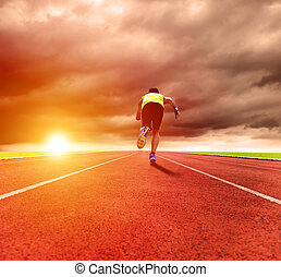 young man running on the track with sunrise background