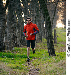 Young Man Running on the Trail in the Wild Forest. Active...