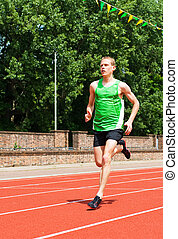 Young Man Running on Track - A young male athlete runs on a...