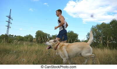 Young man running outdoor with his dog. Labrador or golden retriever jogging with his male owner at nature. Healthy active lifestyle. Slow motion Side view