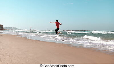 Young man runs along seashore. Summer beach. Freedom...