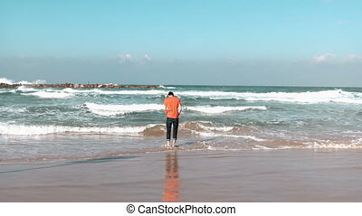 Young man runs from waves on summer sea beach. Bearded...