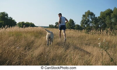 Young man runs outdoors with his labrador. Guy jogging...