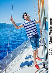 Young man sailing yacht. Sail vacation. People holidays...