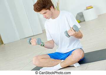 Young man sat on the floor holding weights