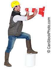 Young man screaming in a traffic cone