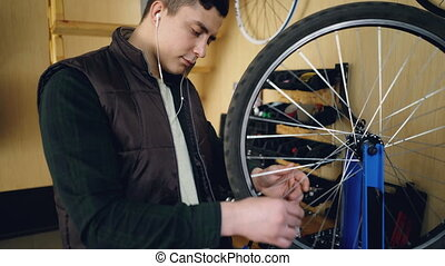 Young man self-employed mechanic is fixing bicycle wheel in...