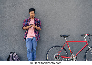 bfd104085 Young man sending a text while standing with his bike. Young Asian man in a plaid  shirt ...