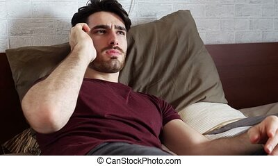 Young man sending voice message on the phone on bed - Young...