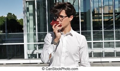 Young man sending voice message with cell phone