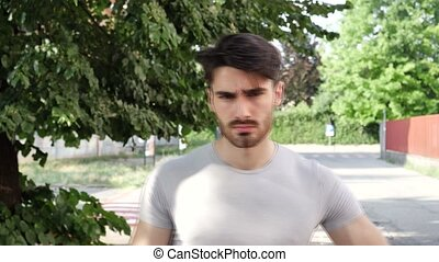 Young man serious with arms crossed, outdoor - Handsome...