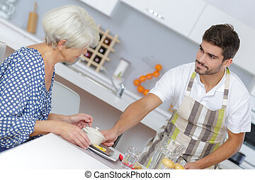 Young man serving meal to elderly lady