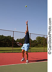 Young man serving tennis ball