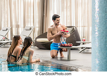 Young man serving with champagne two women at the swimming pool