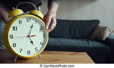 Young man sets the correct time on big yellow clock. Living room interiors