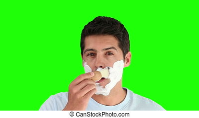 Young man shaving against a green screen