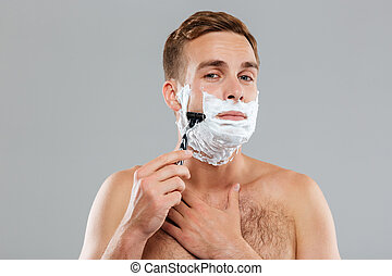 Young man shaving and looking at camera