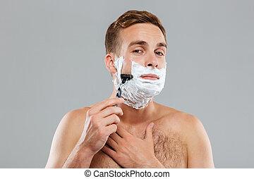 Young man shaving and looking at camera