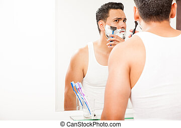 Young man shaving his beard with a razor
