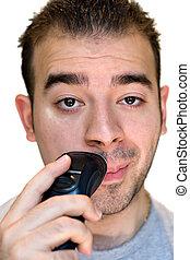 Young Man Shaving - A closeup of a young man shaving his...