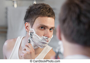 Young man shaving with razor shave looking in a mirror
