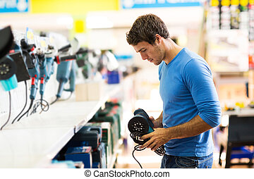 young man shopping for sander in hardware store