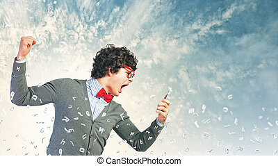 Young man shouting at his mobile phone