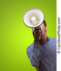 Young Man Shouting On Megaphone against a green background