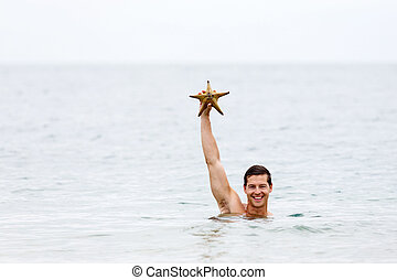young man showing a starfish