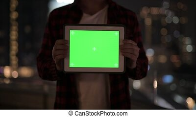Young Man Showing Digital Tablet Against View Of The City At Night