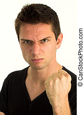 Young man showing fist and looking very aggressive