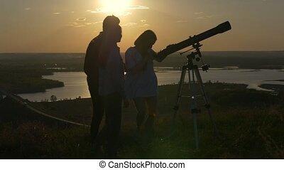 Young man showing friends beautiful view through telescope...