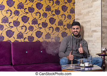 Young Man Showing Thumb Up With Hookah Shisha