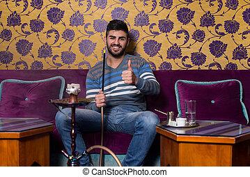 Young Man Showing Thumb Up With Hookah Shisha