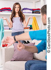 young man showing time to his girlfriend. wife dressing up clothes and getting ready