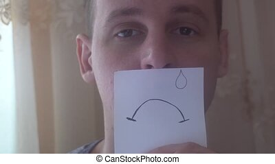 young man shows his emotions with a piece of paper