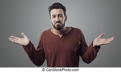 Young man shrugging