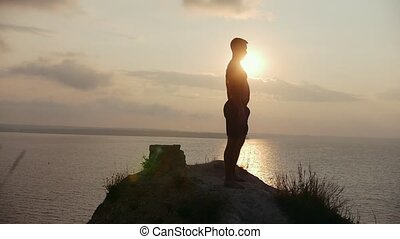Young man silhouette doing squats on the cliff at sunrise,...