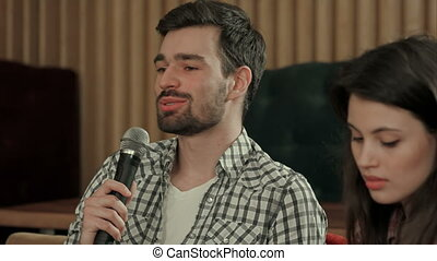 Young man singing favourite song in karaoke