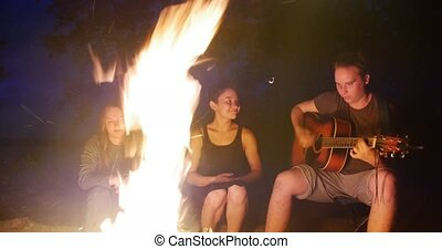 Young man singing songs with guitar and two girls sitting by the campfire in forest
