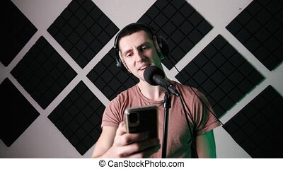 Young Man Sings into Microphone and Records Song while Reading Text from Smartphone in Home Recording Studio. Recording vocals with a dynamic microphone. A room with designer acoustic foam. Creation.