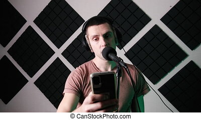 Young Man Sings into Microphone and Records Song while Reading Text from Smartphone in Home Recording Studio. Recording vocals with a dynamic microphone. A room with designer acoustic foam. Timelapse