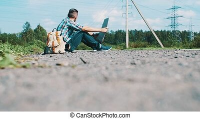 Young man sit hitchhiking at road in countryside with...