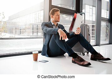 Young man sit on floor and look at cafe menu. Cup of coffee stand on floor with tickets in passport. He wait for flight.
