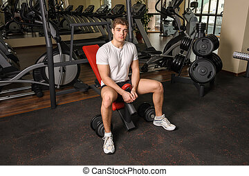 young man sits after workout in gym